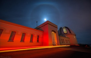 Lights from a passing car paint the Lick Observatory Main Building as the full moon rises over the roofline.